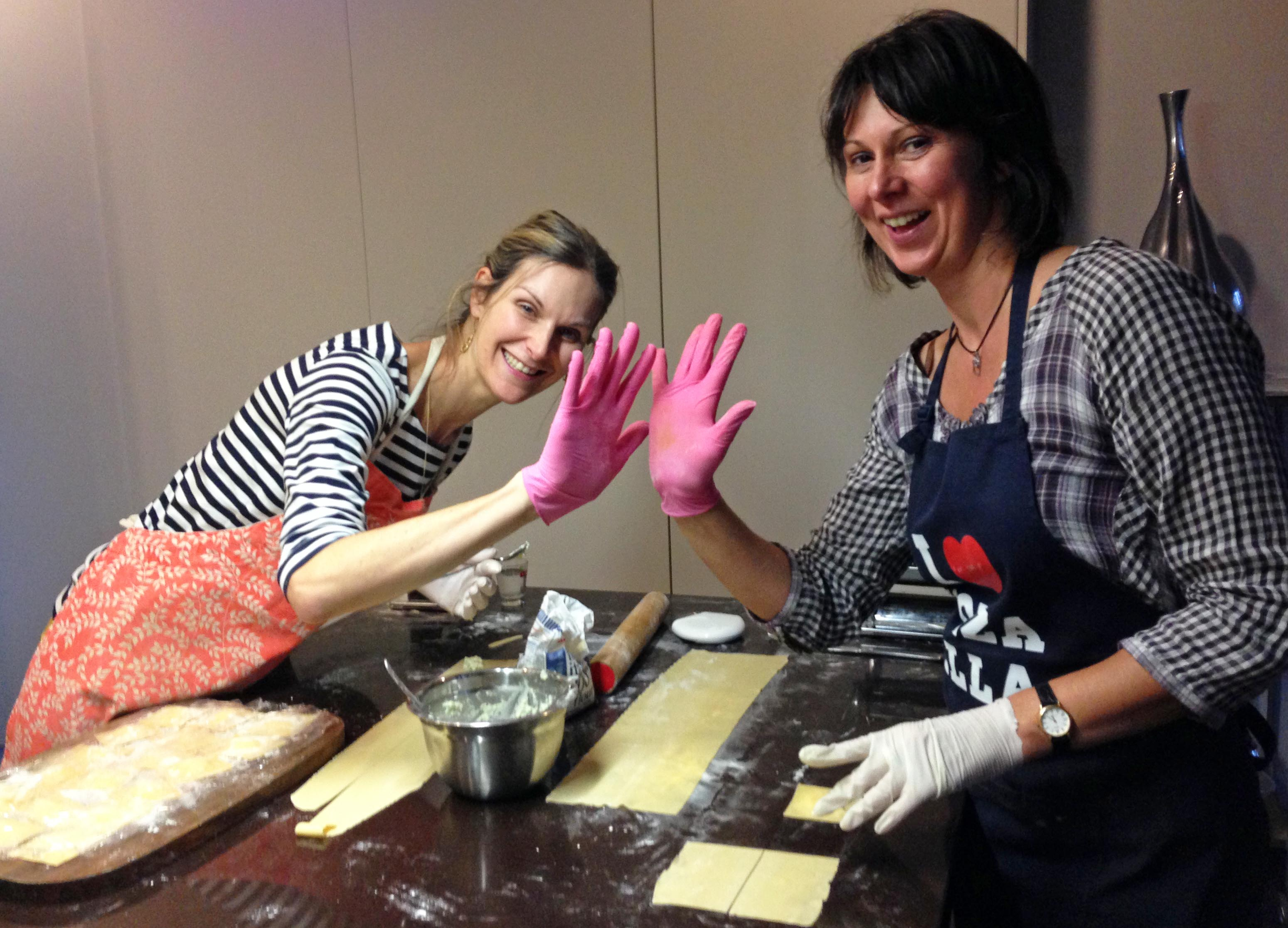 making ravioli wearing pink gloves